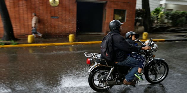 Un motorista pasa hoy ante la Embajada de España en Venezuela.