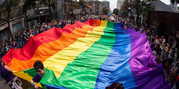 """A giant rainbow flag is carried on Robson Street during the Vancouver Pride Parade on August 6, 2017. The Royal Canadian Mint says it plans to celebrate a 1969 government act that """"initiated the decriminalization of homosexuality in Canada."""""""