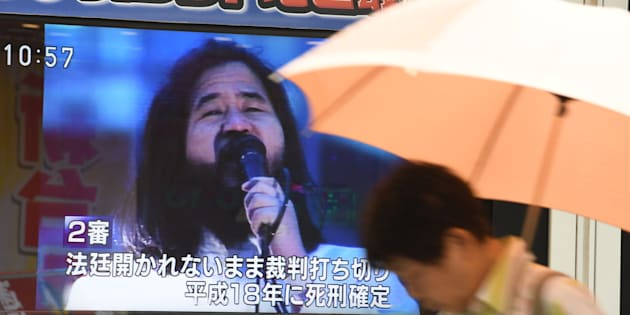 麻原彰晃死刑囚への死刑執行を伝えるTVモニターの前を通り過ぎる人(7月6日撮影)