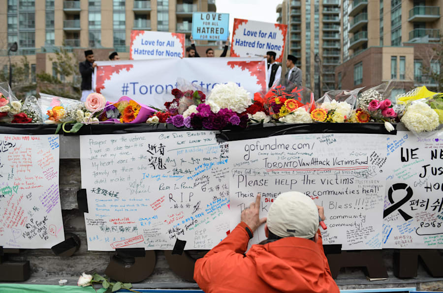 A man writes a message at a memorial on Yonge Street the day after a suspect drove a rented van down sidewalks, striking pedestrians in Toronto.