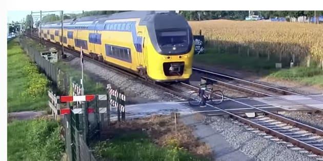 踏切内で、自転車が列車と接触しそうになる瞬間