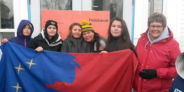 Noretta Miswaggon, third from right, and Pimicikamak Chief Cathy Merrick, far right, hold a Pimicikamak flag with teenagers Cherish Blacksmith, Theodra Thomas, Athena Gamblin and Bethany Ross, at Jenpeg Generating Station in northern Manitoba in 2014.