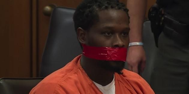 粘着テープで口をふさがれたフランクリン・ウィリアムズ被告