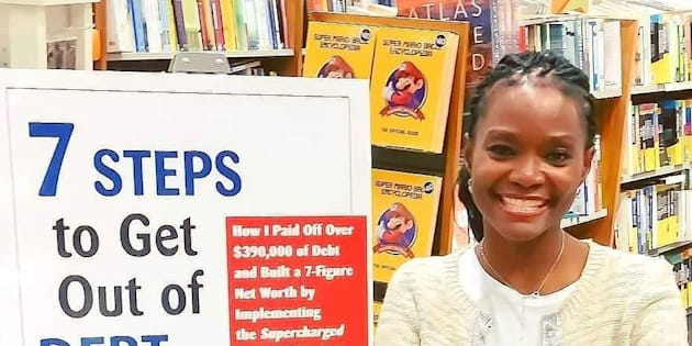 "Adeola Omole is pictured next to a sign for her book, ""7 Steps to Get Out of Debt and Build Wealth"" in this undated handout photo."