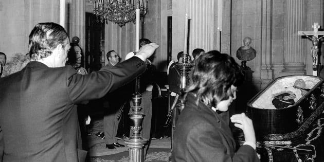 Un hombre hace el saludo fascista ante el cuerpo de Francisco Franco, mientras una mujer se persigna ante el ataúd, en una imagen del 22 de noviembre de 1975.