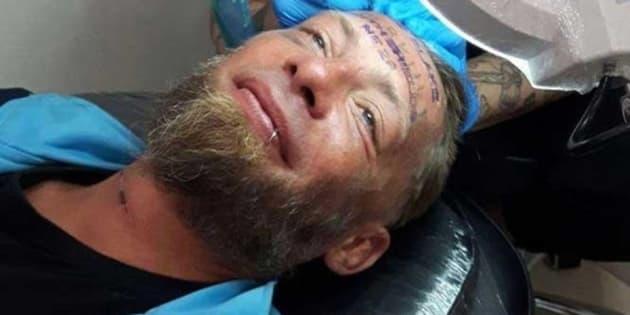 El indigente, llamado Tomek, mientras le realizaban en tatuaje, en una imagen que ha sido profusamente compartida en las redes sociales.