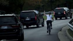Una ciclista rincorre l'auto di Trump per mostrargli il dito