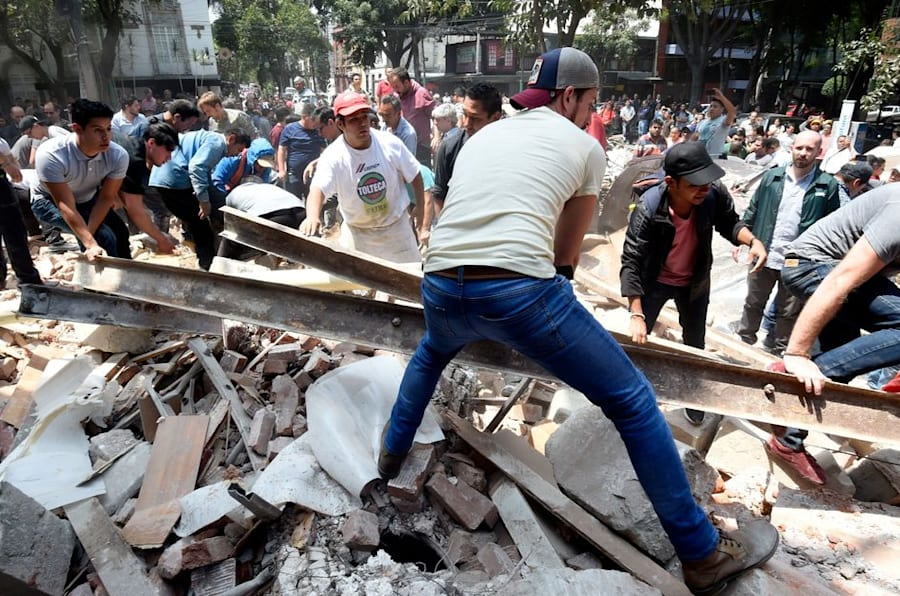 TOPSHOT - Rescuers, firefighters, policemen, soldiers and volunteers remove rubble and debris from a flattened building in search of survivors after a powerful quake in Mexico City on September 19, 2017. A devastating quake in Mexico on Tuesday killed more than 100 people, according to official tallies, with a preliminary 30 deaths recorded in the capital where rescue efforts were still going on. / AFP PHOTO / YURI CORTEZ        (Photo credit should read YURI CORTEZ/AFP/Getty Images)
