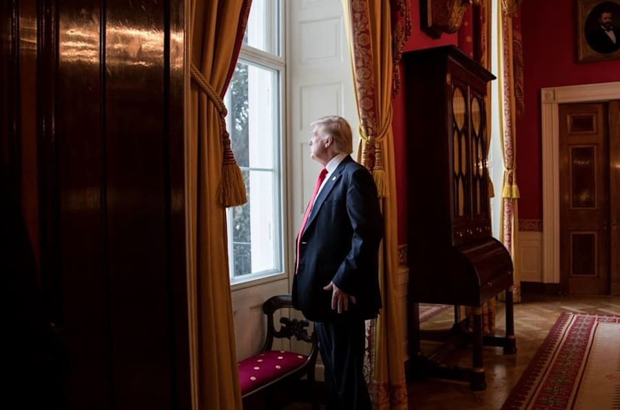 President Donald Trump looks out of the Red Room window onto the South Portico of the White House grounds on Jan. 20, 2017, before departing the White House for his inauguration.