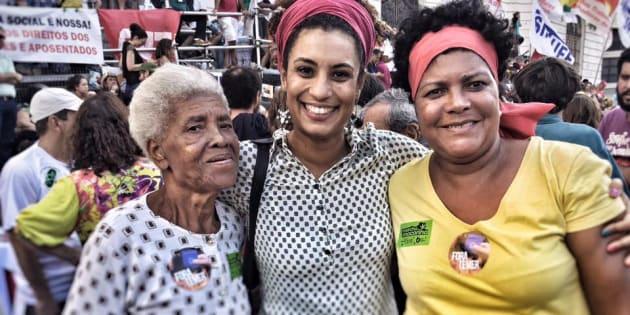 Marielle Franco posa ao lado de duas eleitoras da mesma família e de gerações diferentes.