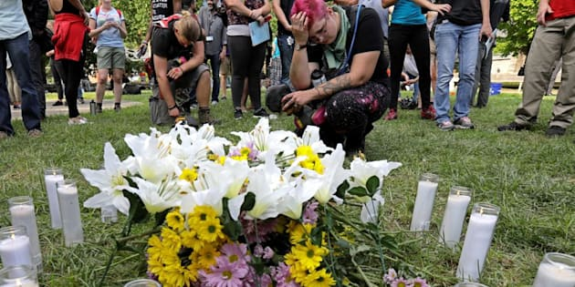 "People pay their respects at a vigil where 20 candles were burned for the 19 people injured and one killed when a car plowed into a crowd of counter-protesters at the ""Unite the Right"" rally organized by white nationalists in Charlottesville, Virginia."