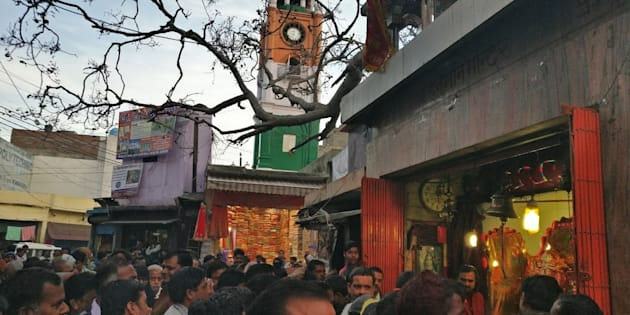 People crowd around a temple in Kasganj, overlooking the clock tower, as it is visited by the BJP's candidate, Devendra Singh Rajput, in the busy Chamunda market of the city.