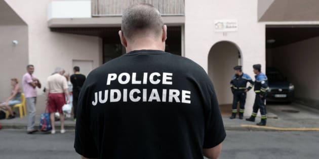 Un agente de la Policía Judicial, junto al edificio donde han muerto cinco miembros de la misma familia en Pau (Francia).