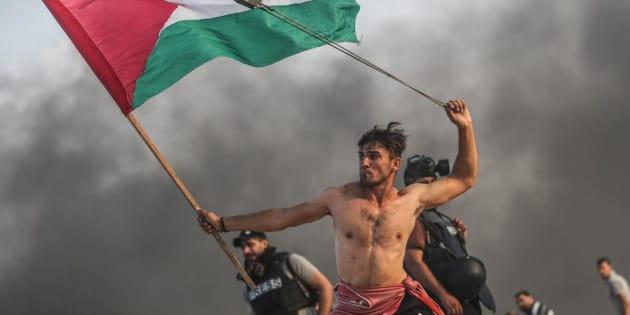 Aed Abu Amro, lanzando piedras y enarbolando la bandera de Palestina en una protesta en Gaza, el pasado día 22.