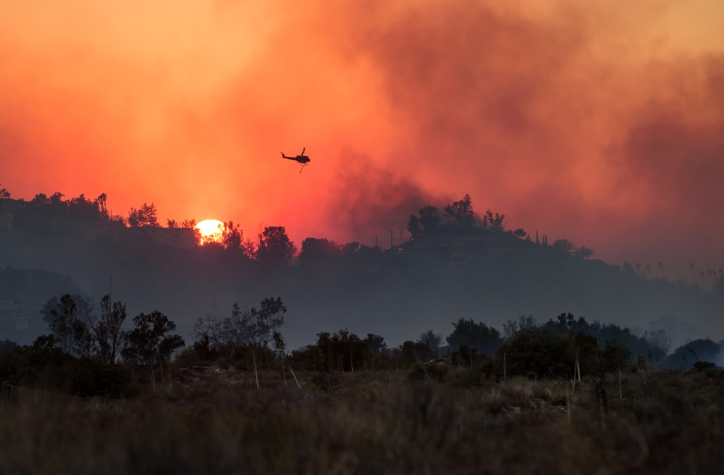 Firefighting Helicopter Flies Over The Creek Fire As The Sun Sets In Picture Id886861764