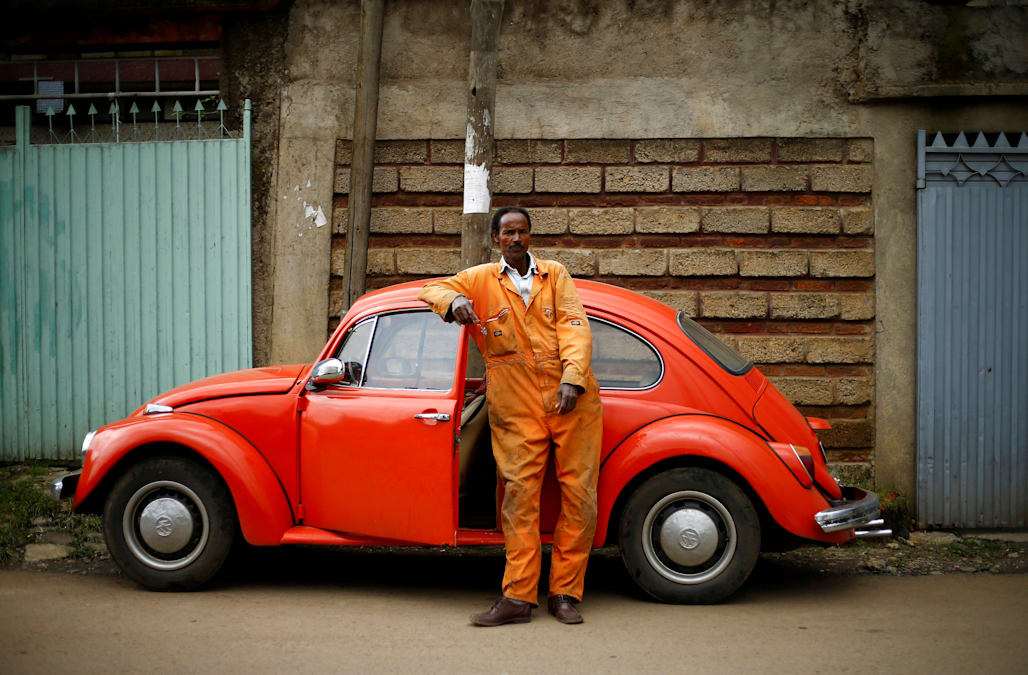"""Image result for In Addis Ababa, Ethiopia, cranky, 50-year-old Volkswagen Beetles enjoy a kind of life after death; their parts are never discarded but re-used to keep the city's remaining Beetles on the road. Here's a look Pictured: Mechanic Ishetu Kinfe poses next to his 1965 Volkswagen Beetle at a garage in Addis Ababa on October 27. He has driven the car for 19 years. Says Kinfe: """"I can drive it anywhere because it is strong, easy to maintain, and affordable."""" (All photos: Tiksa Negeri/Reuters)  Read more at: http://www.nationalreview.com/slideshows/volkswagen-beetle-cars-addis-ababa-ethiopia"""