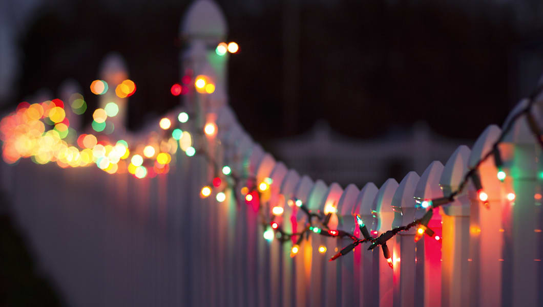 a string of multi colored christmas lights are strung across a white plastic fence