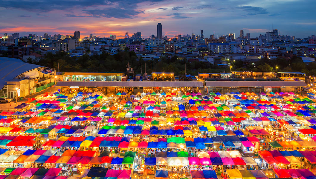 Night scene of colorful tent and cityscape at Chatujak market secondhand market in Bangkok , Thailand