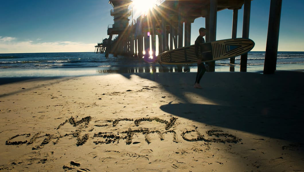 The holiday greeting 'Merry Christmas' written in sand along a sunny California beach, with the pier, sun flare and surfer in the background.