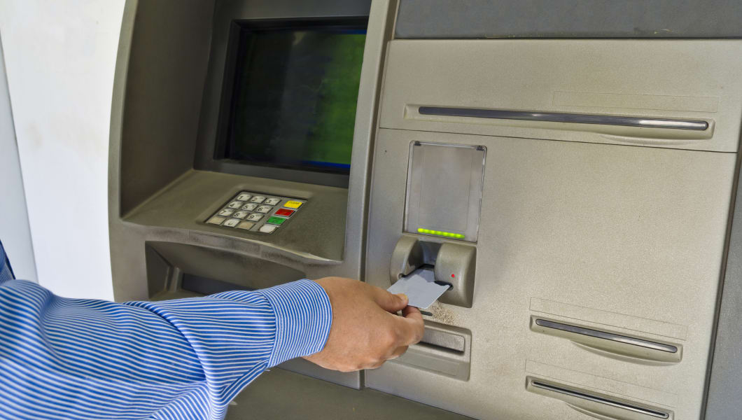 Hand of male inserting his card into an old ATM machine.
