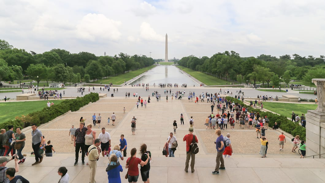 Washington DC, USA - May 16, 2014: People in front of Lincoln Memorial building with far background is Washington Monument with green tree and long reflecting pool.