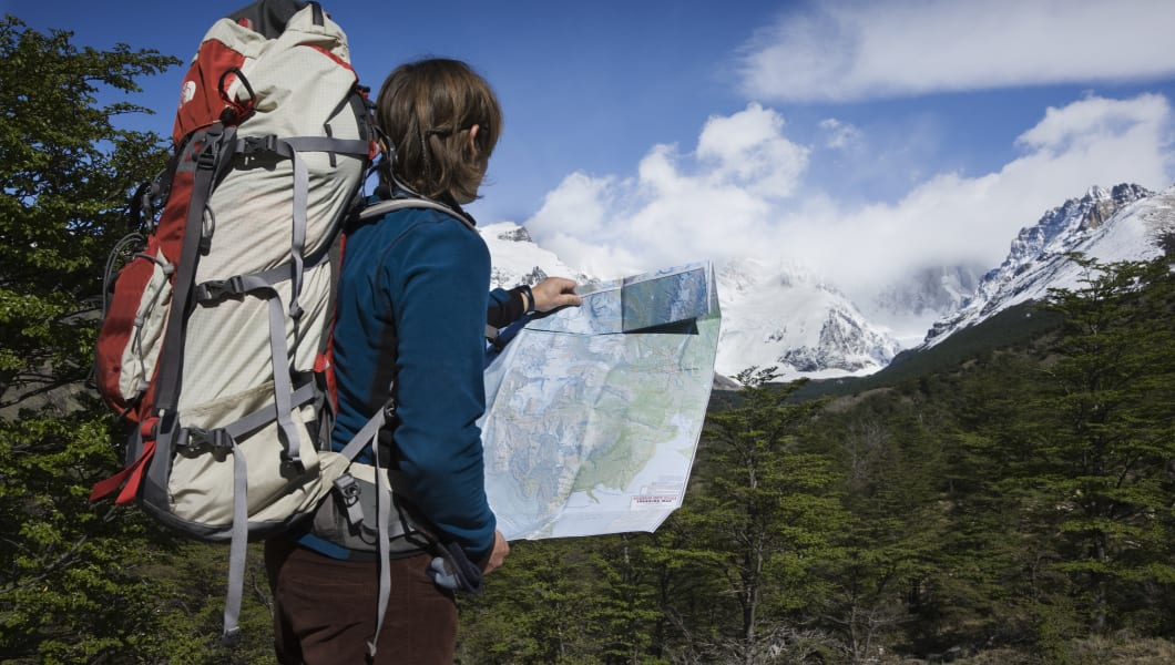 Tourist using map to navigate towards Glacier Grand which forms part of the Patagonian South Ice field. Los Glaciares National Park, Andes Mountain Range, Santa Cruz Province, Argentina. This is a World Heritage site.