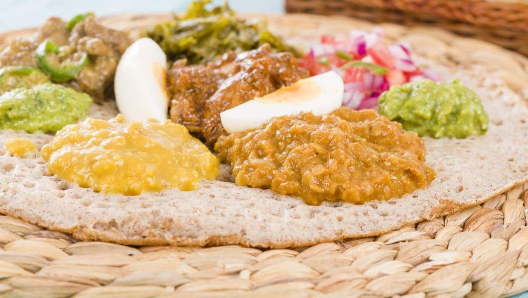 Injera (sourdough flatbread) with doro wat (red chicken stew), yebeg alicha (mild lamb stew), misir wat (red lentils puree), kik alicha (yellow split peas) and gomen (collard greens)