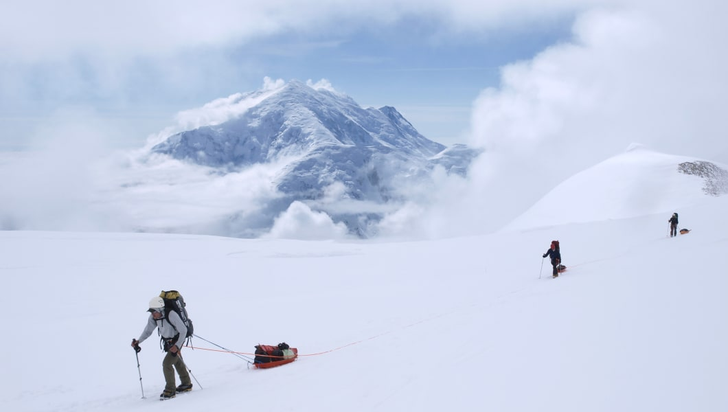 A team of mountaineers are roped up while crossing the upper Kahiltna glacier on their way to 14.000 feet camp Mount McKinley in Alaska. The rope will prevent a climber from falling deep into a crevasse when a snow bridge suddenly collapses. The other team members can then use the rope to rescue the victim. On the sleds the alpinists carry part of their gear, tents and food. Mount McKinley or Denali is the highest mountain peak in North America, with a summit elevation of 20,237 feet (6,168 m) above sea level. At some 18,000 feet (5,500 m), the base-to-peak rise is considered the largest of any mountain situated entirely above sea level. Measured by topographic prominence, it is the third most prominent peak after Mount Everest and Aconcagua. Located in the Alaska Range in the interior of the U.S. state of Alaska, McKinley is the centerpiece of Denali National Park and Preserve. Mount Hunter is seen in the background.