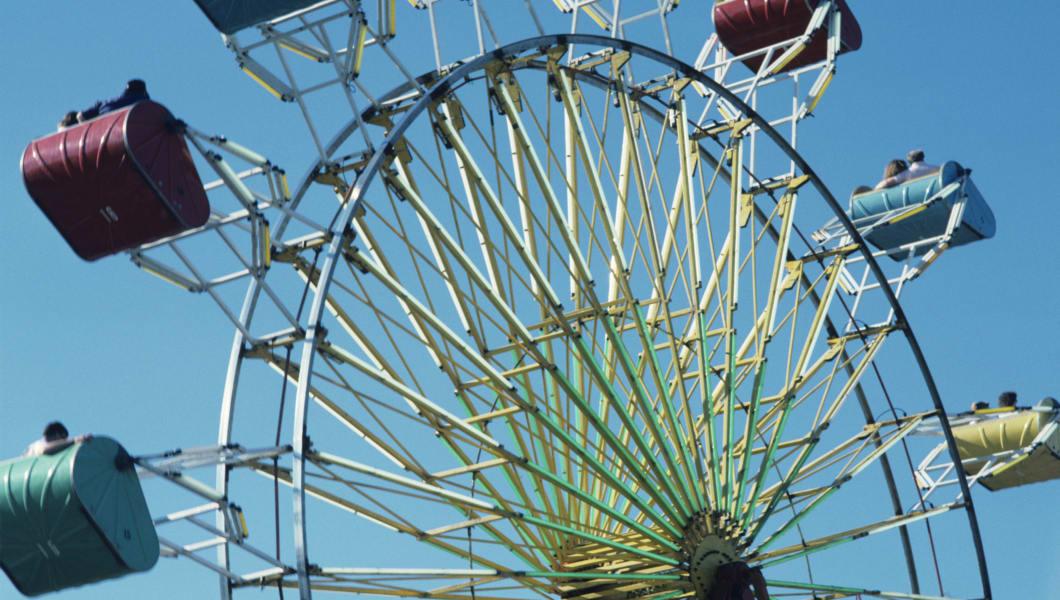 County fair Ferris wheel against blue sky, close-up