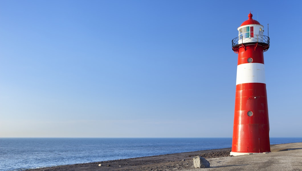 A bright red lighthouse and a clear blue sky.