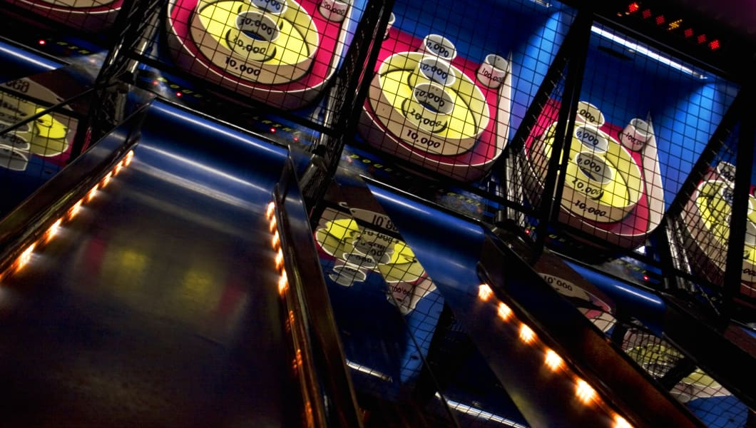 A series of skee-ball games lined up in an arcade.  Try to roll 100,000.