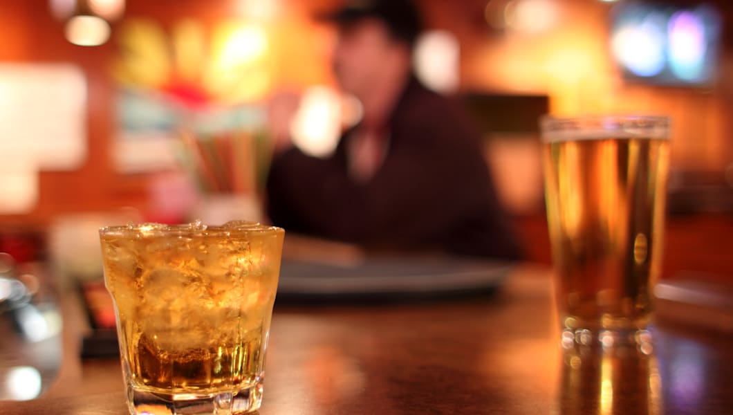 Whiskey on the rocks and a glass of beer in the background at a dive bar.