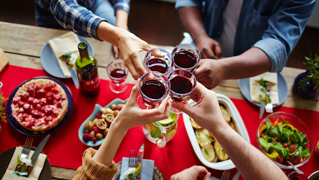 Friends toasting with red wine over served table