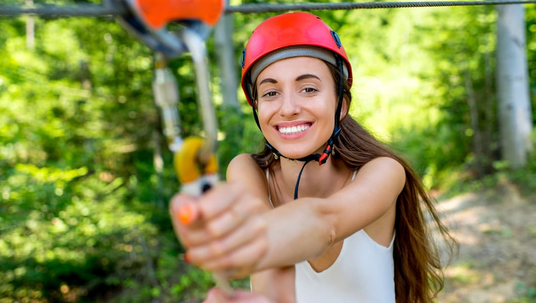 Young and pretty woman in red helmet enjoying riding a zip line in the forest. Active summer sports recareation