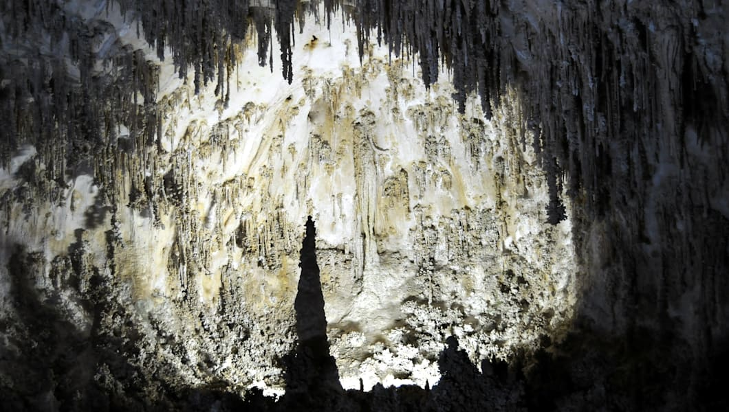 'An amazing cave, part of the second largest cave chamber in the world (more than 1 km long and over 100 meters high), which is located in the Carlsbad Caverns National Park in New Mexico, USA, a UNESCO World Heritage site. Dramatic stalactites and stalagmites are lit to highlight the limestone features.'