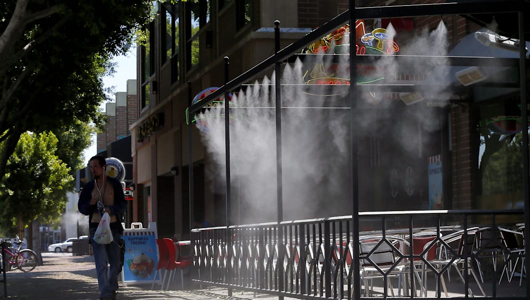 A Pedestrian Walks Past An Empty Patio During Lunch Hour As Misters Spray  In Downtown Tempe