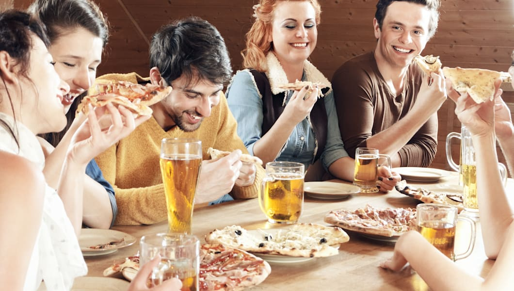 Young group of laughing people eating pizza and drinking beer in a bar