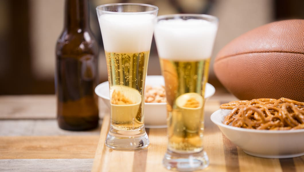 Sports bar, pub setting.  An American football, pretzels, peanuts, beer in glasses and in a bottle are all on the wooden bar counter top.  A dartboard is in the background.  Superbowl party!