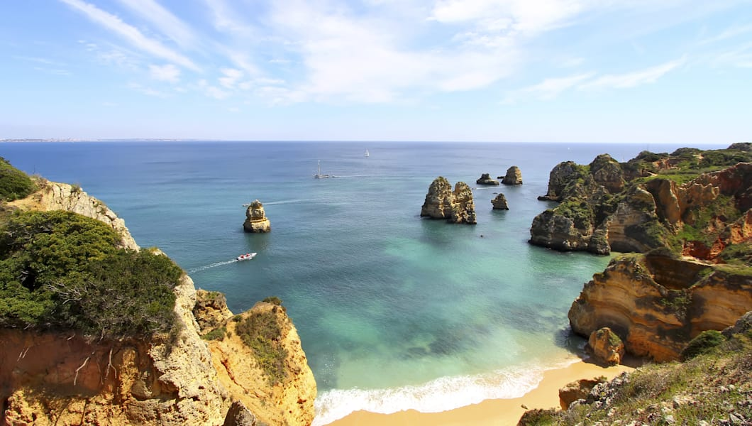 Rocky beach with a foam in the surf, Lagos, Portugal