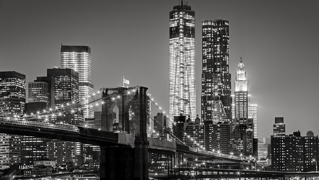 Black & White cityscape by night. View of Brooklyn Bridge, Downtown Manhattan (Lower Manhattan) and the Financial District. NYC skyline with Manhattan skyscrapers lit up at night.
