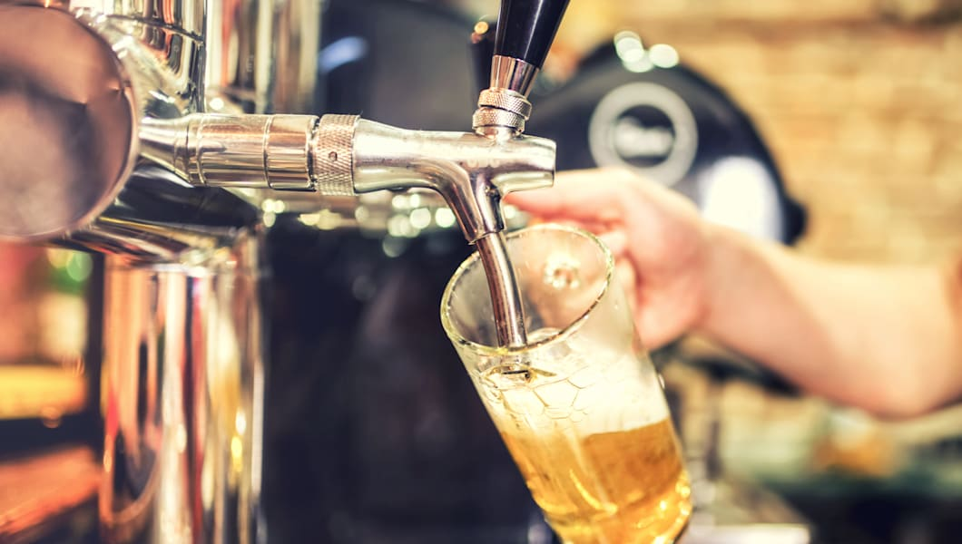 barman hand at beer tap pouring ...