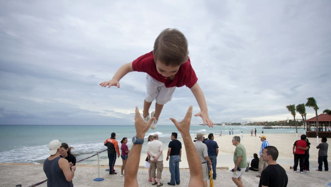 A man throws his son in the air, at a beach in Playa del Carmen October 27, 2011. Hurricane Rina weakened to a tropical storm on Thursday as it swept toward Mexico's Caribbean coast after causing travel chaos and spurring evacuations from island resorts. REUTERS/Victor Ruiz Garcia (MEXICO - Tags: DISASTER ENVIRONMENT TPX IMAGES OF THE DAY)