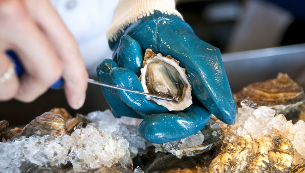 Shucking a fresh sweetwater oyster at an oyster bar in San Francisco