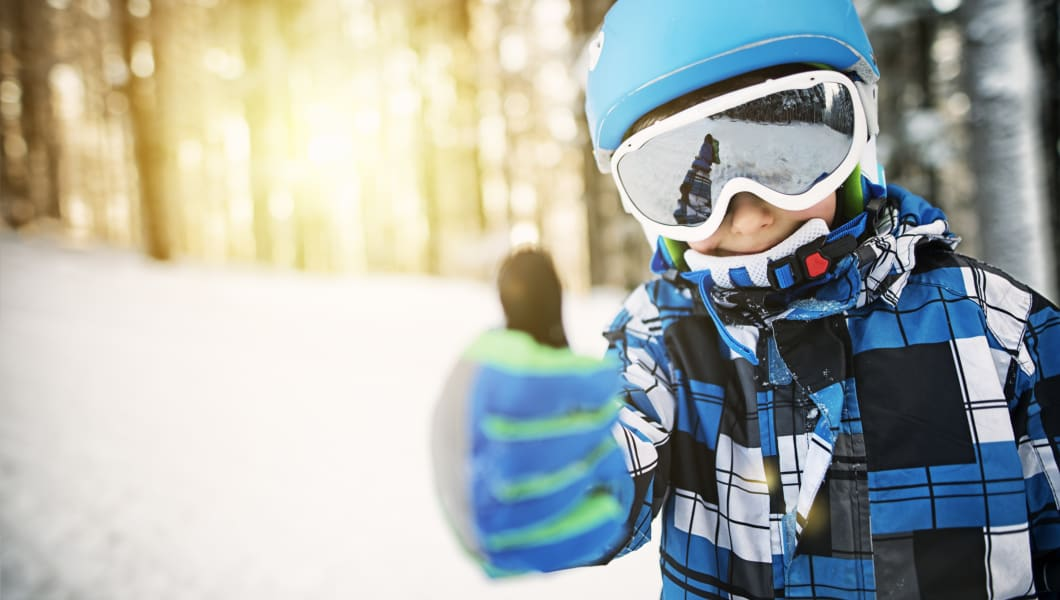 Portrait of a smiling little boy skiing. The boy is smiling and showing thumbs up to the camera. Sun is shining through beautiful frozen trees in the background. Sunny winter day.