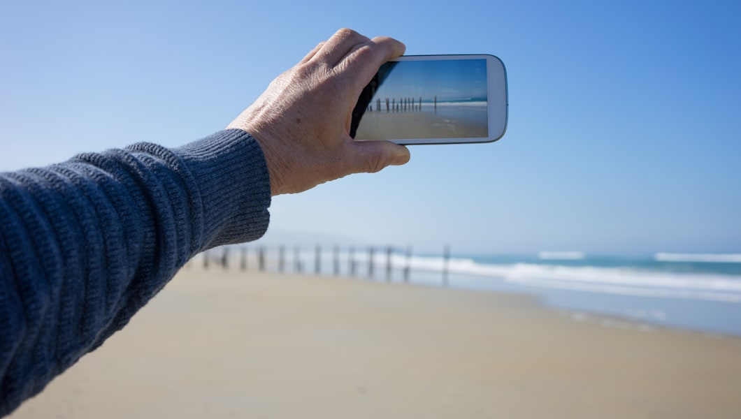 Taking a photo of a beach on a smart phone.