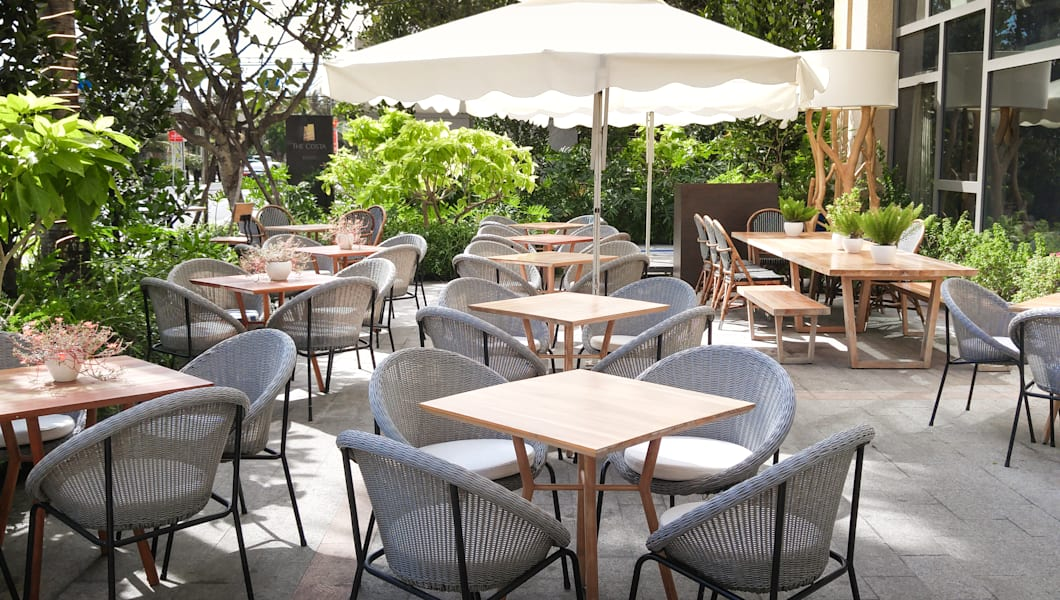 Chairs And Tables Of A Restaurant Seating Outside With Parasols