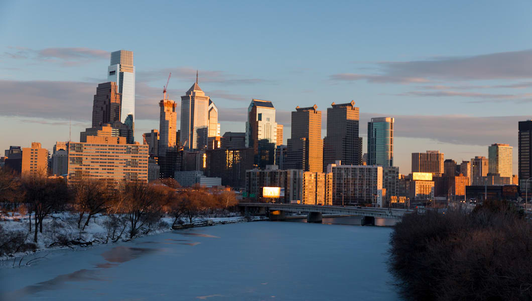 All of Philadelphia covered in snow after winter 2016 snow storm, Schuylkill river completely frozen and downtown skyline on the background during sunset.