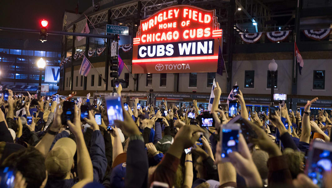 Chicago fans celebrate the Chicago Cubs 8-7 victory over the Cleveland Indians in Cleveland in 10th inning in game seven of the 2016 World Series, outside Wrigley Field in Chicago, Illinois early on November 3, 2016. Ending America's longest sports title drought in dramatic fashion, the Chicago Cubs captured their first World Series since 1908 by defeating the Cleveland Indians 8-7 in a 10-inning thriller that concluded early on November 3. / AFP / Tasos Katopodis        (Photo credit should read TASOS KATOPODIS/AFP/Getty Images)