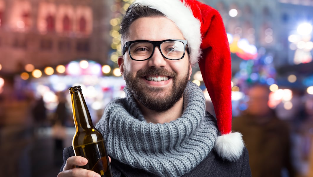 Young man with Santa hat and beer bottle
