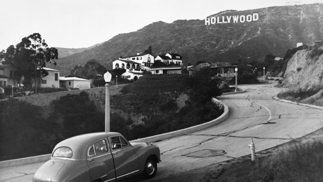 1950s AUSTIN CAR DRIVING UP THE HOLLYWOOD HILLS WITH HOLLYWOOD SIGN IN DISTANCE   (Photo by Charles Phelps Cushing/ClassicStock/Getty Images)